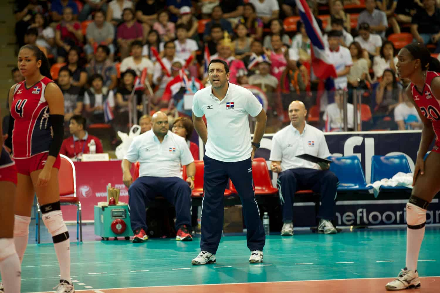 Volleyball coach on sidelines giving instructions to his team