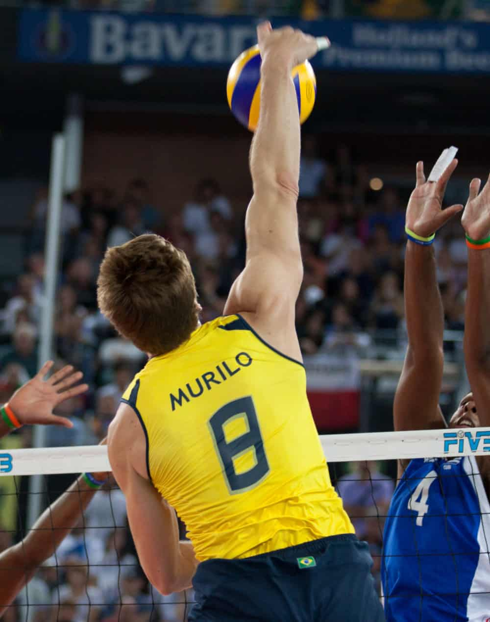 Male volleyball player spiking a ball over the net