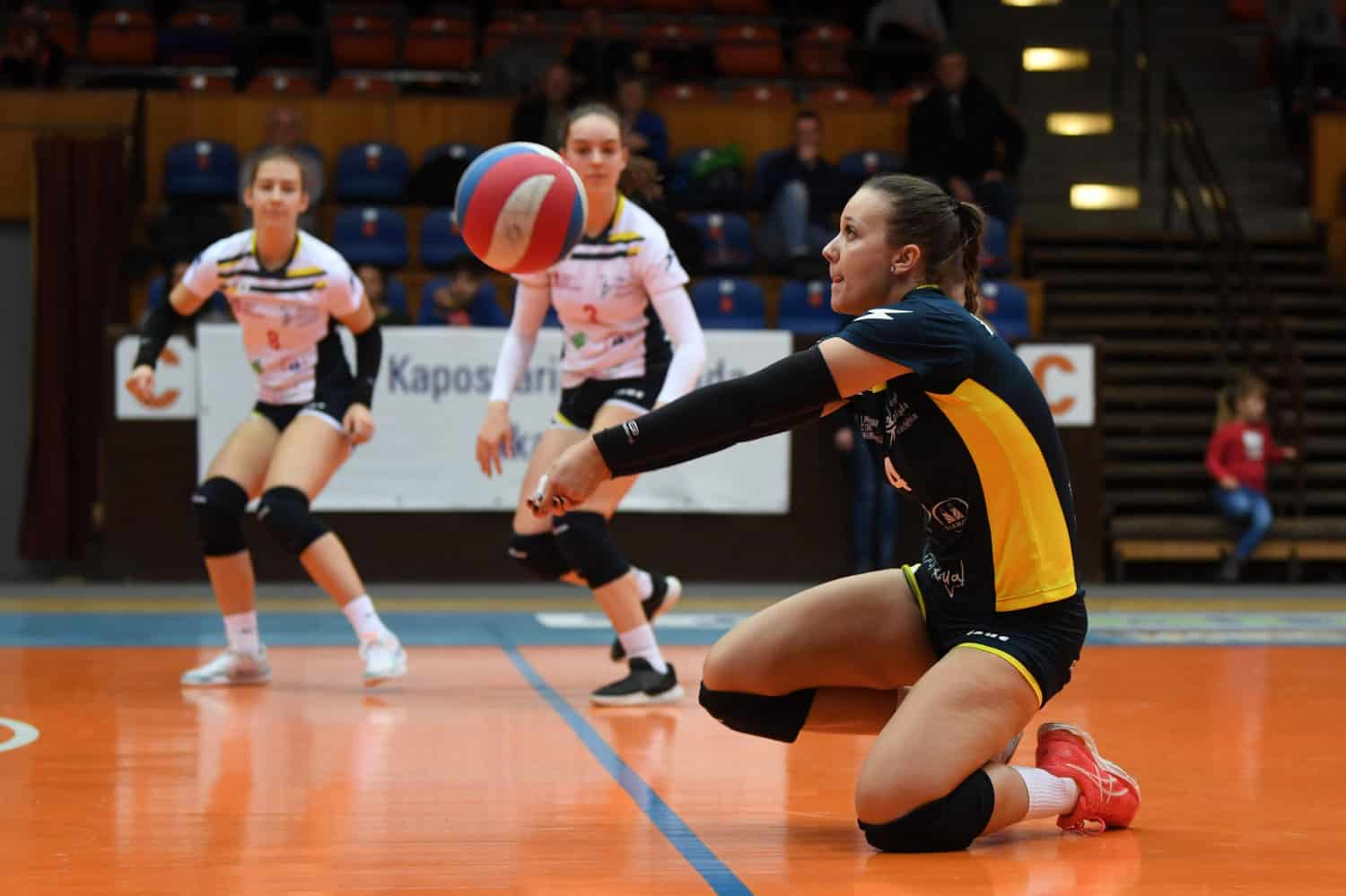Volleyball player on her knees digging a ball
